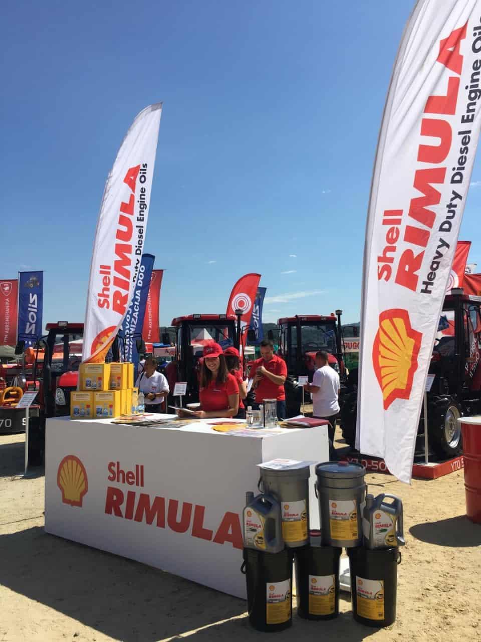 Shell Rimula ulja na štandu, traktori u pozadini, ljudi predstavljaju ulja